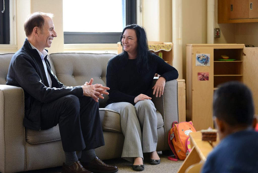 Two smiling adults converse while sitting on a sofa in a preschool classroom