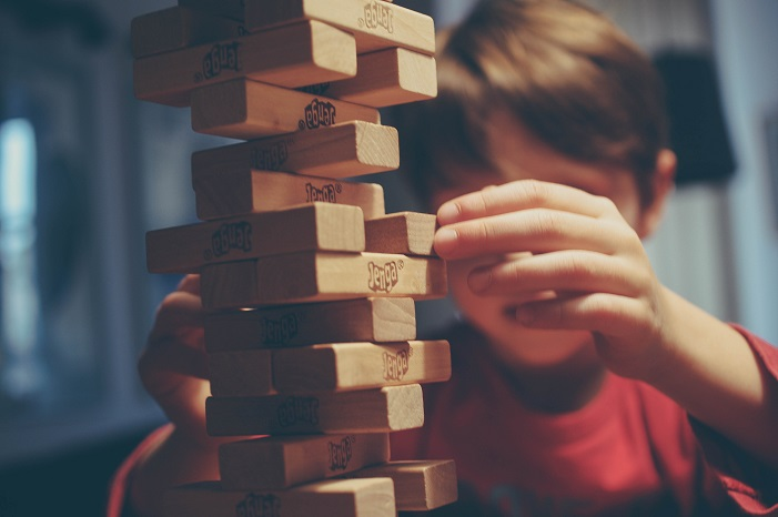 A child pulls a Jenga block from a tower of blocks
