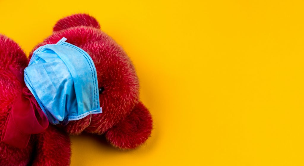 A red teddy bear against a yellow background wearing a blue surgical mask