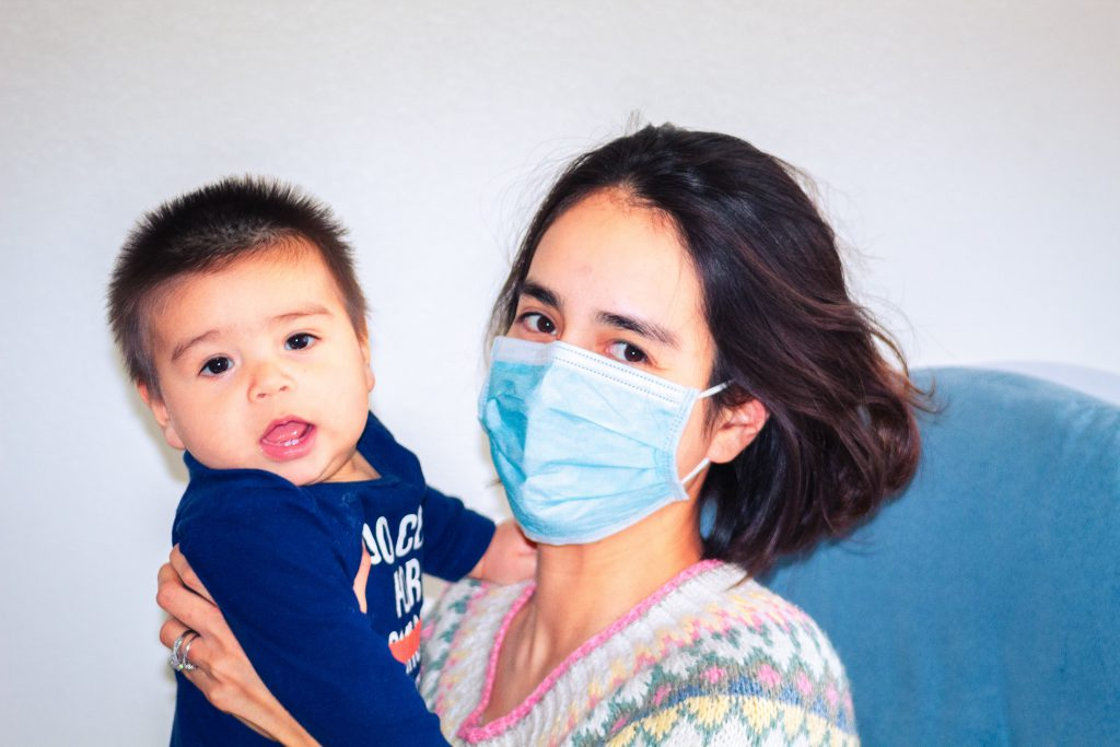 A woman wearing a face mask holds a baby